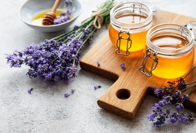 Pots avec du miel et des fleurs de lavande fraîches sur fond de béton