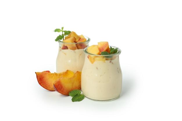 Pots avec du yaourt à la pêche et des ingrédients isolés sur fond blanc