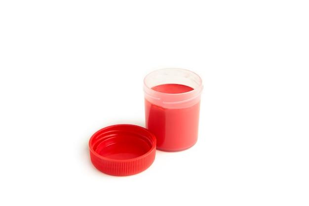 Pots de gouache rouge et peintures acryliques de couleurs primaires sur fond blanc.