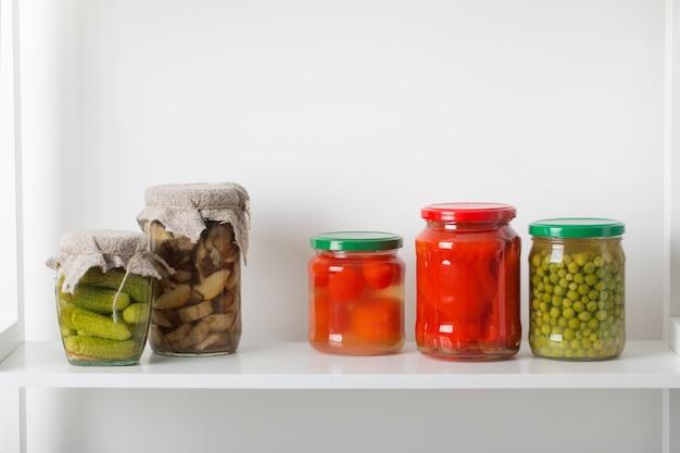 Pots de légumes marinés sur tableau blanc