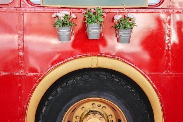 Pots avec des plantes de décoration suspendus à un bus rouge dans une exposition de voitures anciennes.