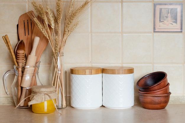 Pots pour céréales avec couvercles en bois, couverts en bois et fleurs séchées et épillets dans une bouteille sur la table de la cuisine, de style scandinave. ustensiles de cuisine et décoration écologiques, mise au point sélective