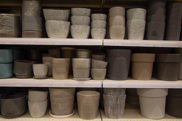 Des pots pour fleurs de teintes claires et foncées se trouvent sur trois étagères