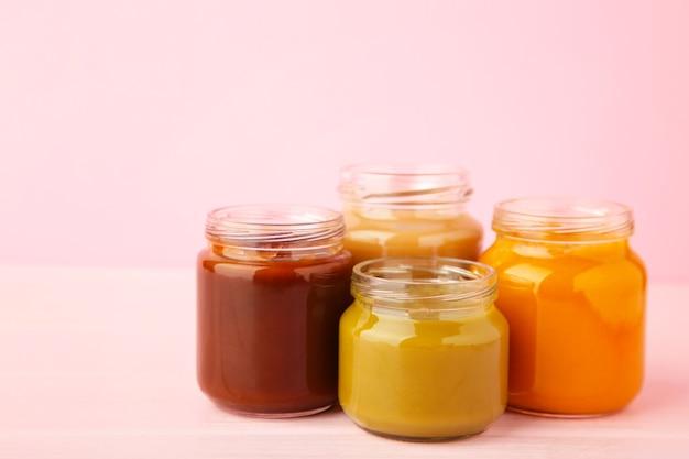 Pots de purée pour bébé sur rose. purée de fruits et légumes