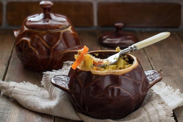 Pots de ragoût de pommes de terre au poulet et légumes sur fond de bois avec serviette en lin