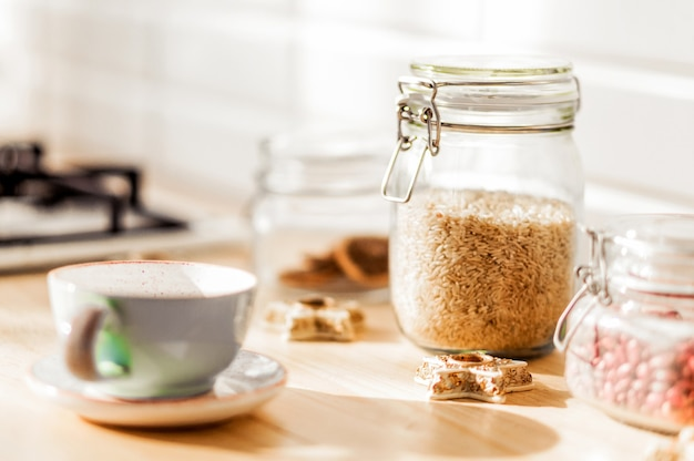 Des pots de riz et de haricots sont dans la cuisine. à côté des canettes, il y a une tasse de thé sur une soucoupe et des biscuits. photo horizontale
