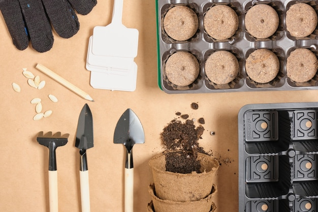Pots de tourbe, pelles, pots, assiettes et graines de courgettes sur papier craft vue de dessus, plantation de printemps, tout pour la croissance des semis