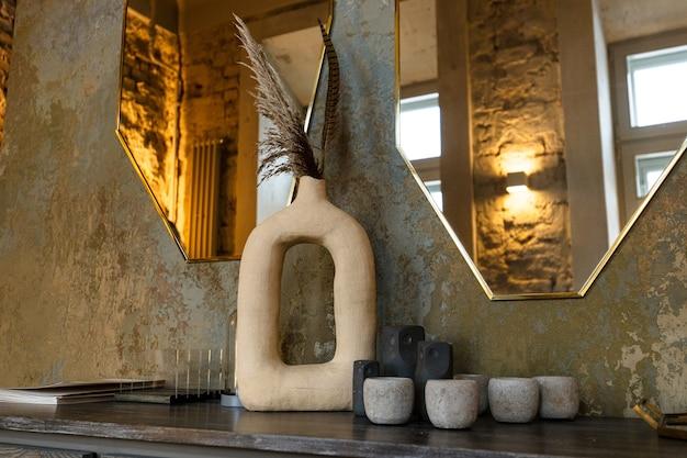 Des pots et des vases de différentes formes en pierre se dressent sur le piédestal sur fond de miroir...