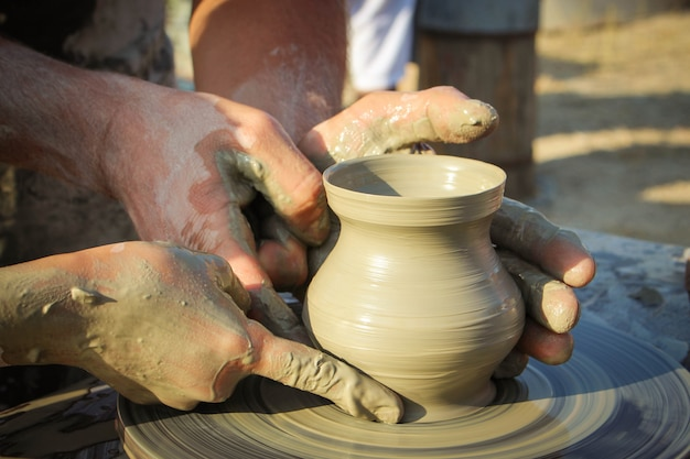 Potter aide l'enfant à fabriquer un vase d'argile