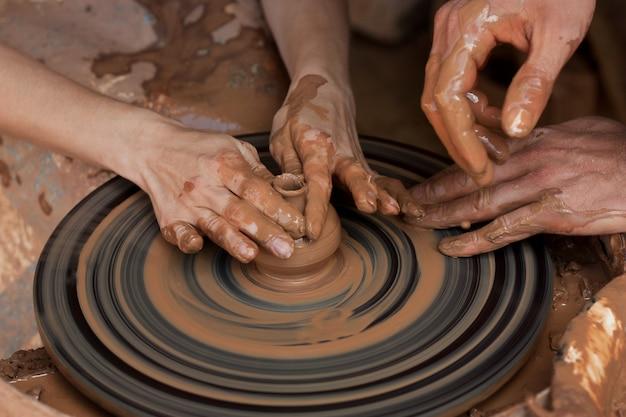 Potter apprend à sculpter dans un pot en argile sur un tour de potier