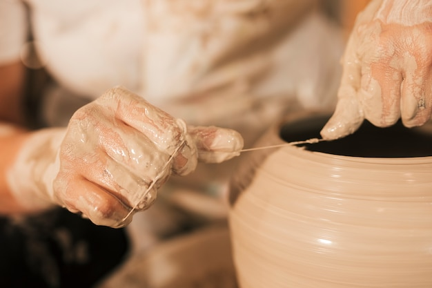 Potter coupe les bords de la poterie avec du fil sur le rouet