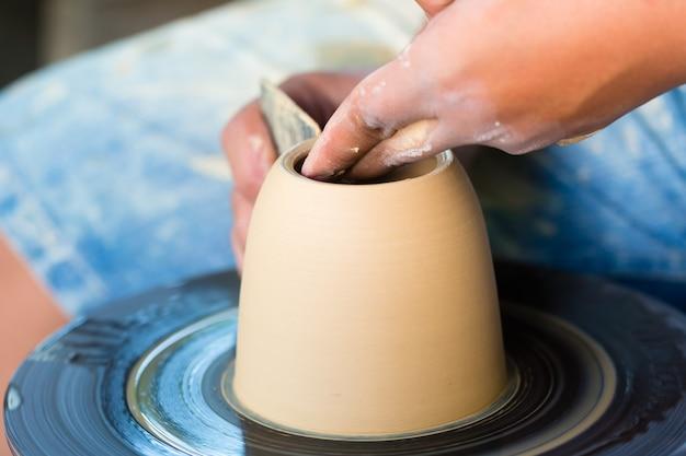 Potter créant un bol en argile sur une roue en rotation