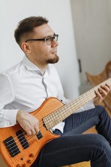 Pottret de jolie jeune homme jouant de la guitare assis sur un canapé à la maison