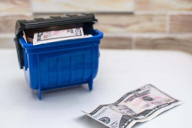 Poubelle bleue, paquets de dollars sur fond clair