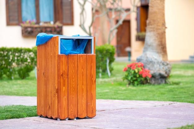 Poubelle en bois jaune à l'extérieur sur le côté du trottoir dans le parc. conteneur à ordures à l'extérieur.