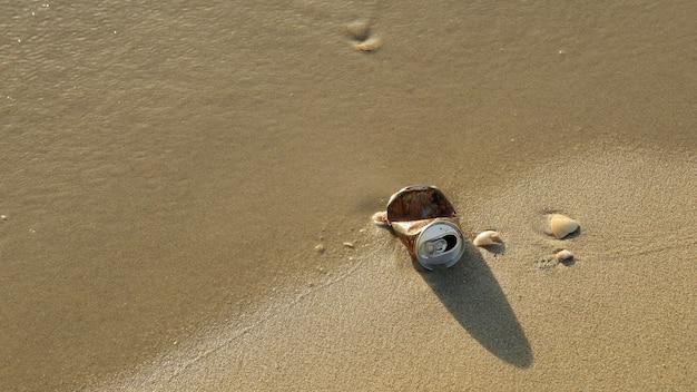 Poubelle, canette d'aluminium, sur la plage avec des coquillages sur le sable en été.