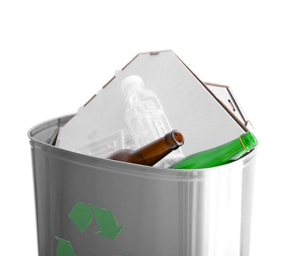 Poubelle avec des ordures sur une surface blanche