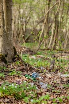 Poubelle en plastique dans la forêt. nature cachée. récipient en plastique couché dans l'herbe