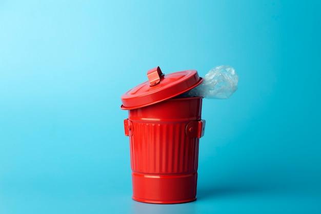 Poubelle en plastique et déchets dans une poubelle sur fond bleu. concept de tri et de recyclage des déchets et du plastique