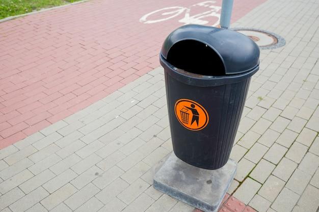 Poubelle publique noire sur le bord de la route. concept de contrôle infectieux.