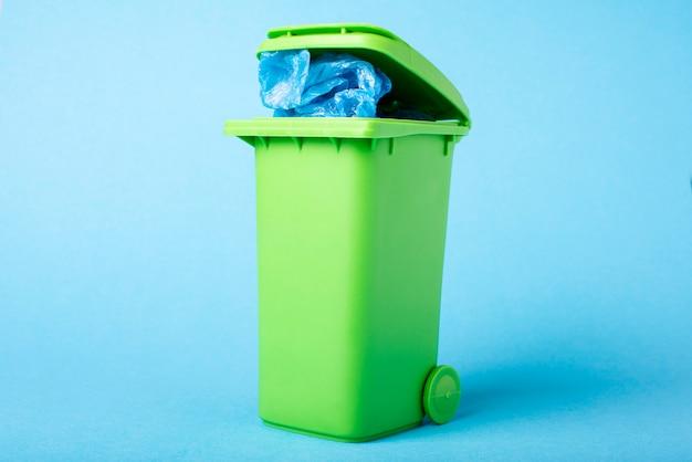 Poubelle verte sur fond bleu. polyéthylène.