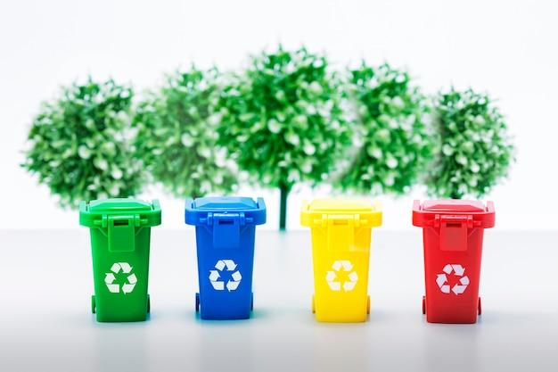 Poubelles avec déchets triés contre les arbres verts. écologie et recyclage.