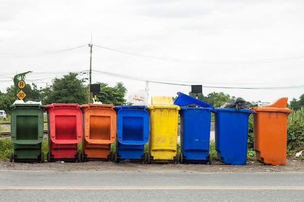 ฺ des poubelles de différentes couleurs posées dans la rue