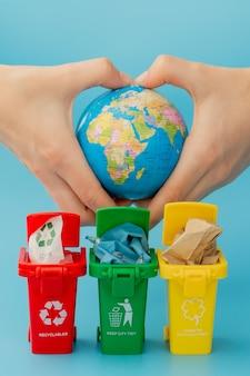 Poubelles de recyclage jaunes, vertes et rouges avec symbole de recyclage sur fond bleu.