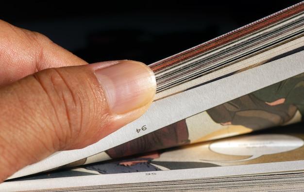 Un pouce feuilletant les pages d'une bande dessinée, mise au point sélectionnée.