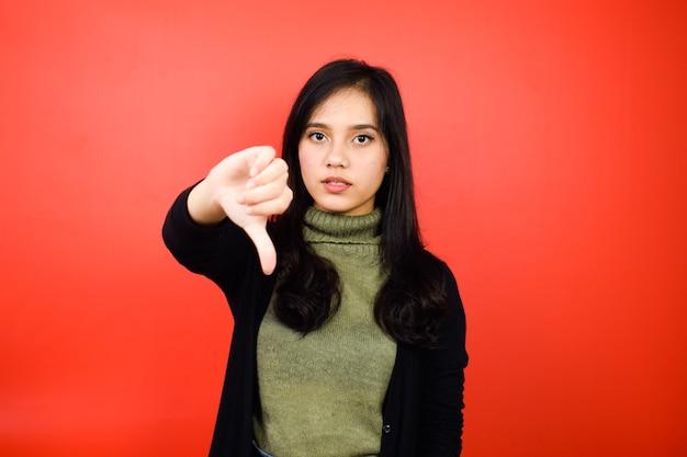 Pouce vers le bas de jeunes belles femmes asiatiques à l'aide d'un pull noir avec fond isolé rouge