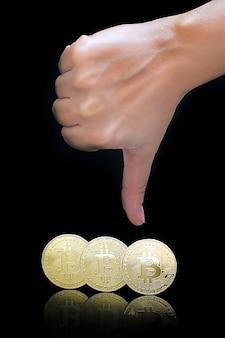 Le pouce vers le bas signe de la main. bitcoins. bitcoins et nouveau concept d'argent virtuel. le bitcoin est une nouvelle monnaie.