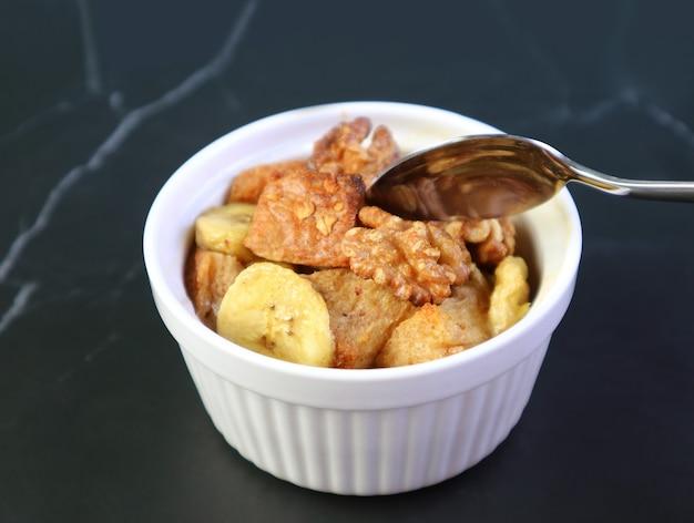 Pouding au pain aux bananes et aux noix dans un bol en céramique isolé sur tableau noir