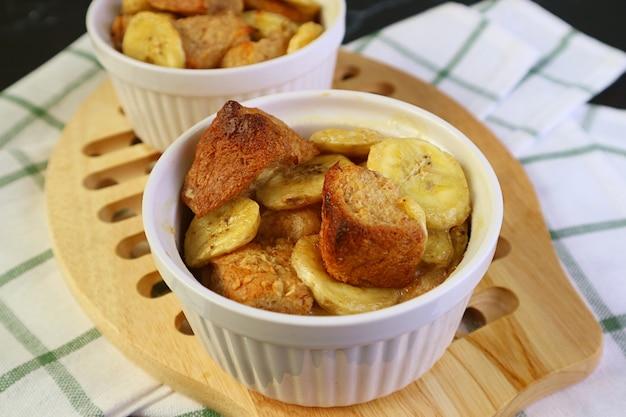 Pouding au pain aux bananes maison cuit au four dans un bol en céramique sur planche à pain en bois