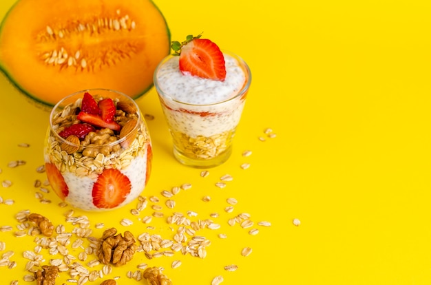 Pouding au yaourt chia avec fraises, flocons d'avoine et noix dans un verre jaune