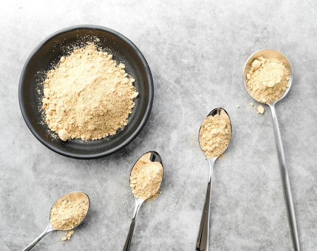 Poudre d'aliments biologiques dans un bol et des cuillères