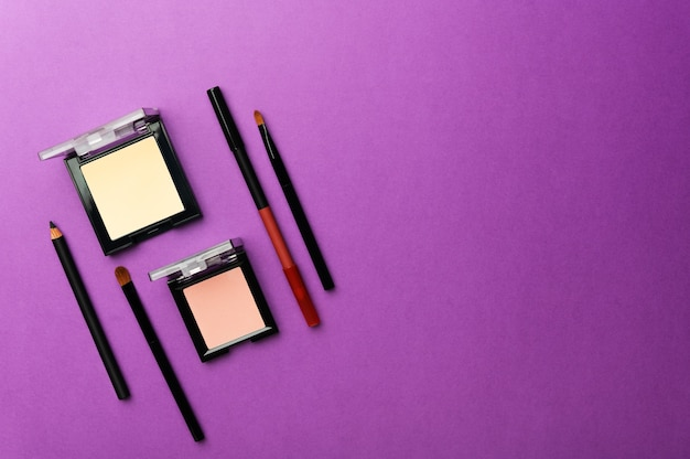 Poudre beige pour le visage, fard à joues, eye-liner et pinceau de maquillage professionnel sur violet
