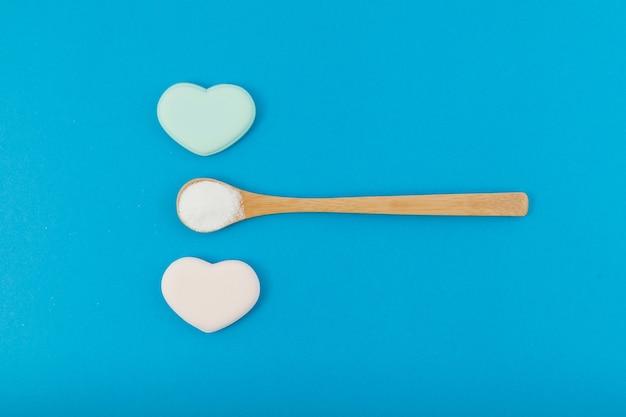 Poudre blanche dans une cuillère en bois sur fond bleu avec des coeurs.