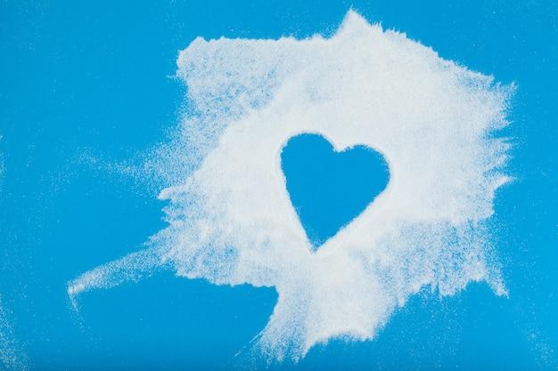 La poudre blanche est dispersée de manière chaotique sur la surface bleue l'espace vide en forme de coeur