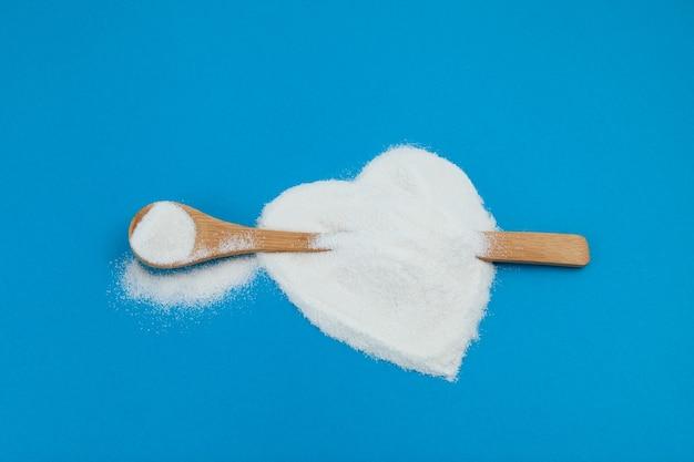 La poudre blanche est dispersée sur la surface bleue en forme de coeur. cuillère en bois avec du collagène ou des protéines. complément alimentaire sain.