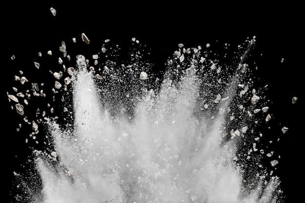 Poudre blanche avec explosion de petites pierres sur fond noir.