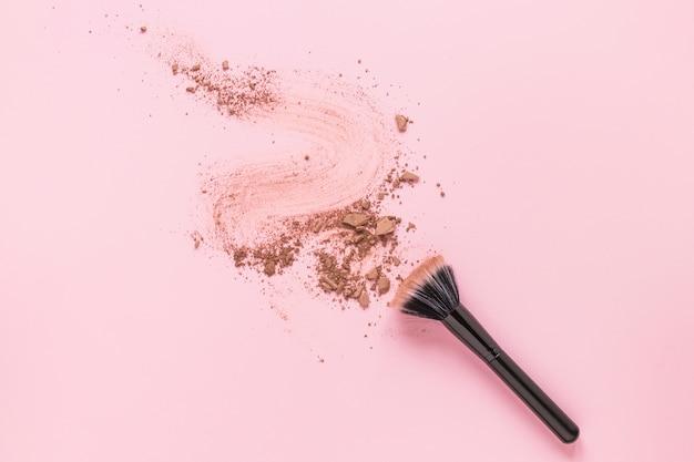 Poudre brosse avec de la poudre dispersée émiettée sur la table