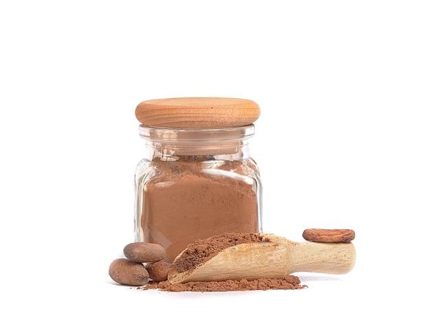 Poudre de cacao dans un bocal en verre et fèves de cacao