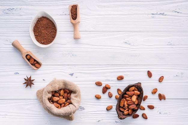Poudre de cacao et fèves de cacao sur fond en bois.