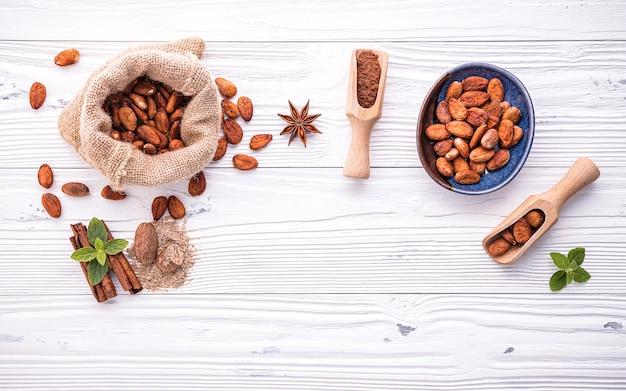 Poudre de cacao et fèves de cacao sur une table en bois.