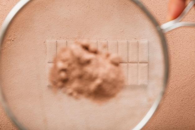 Poudre de cacao saupoudrée du tamis sur une barre de chocolat