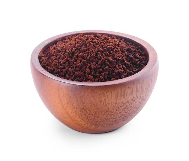 La poudre de café éclater dans un bol sur fond blanc