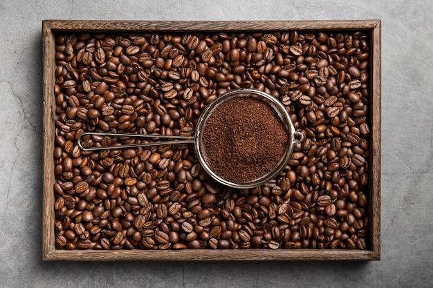 Poudre de café à plat dans une passoire et des grains de café