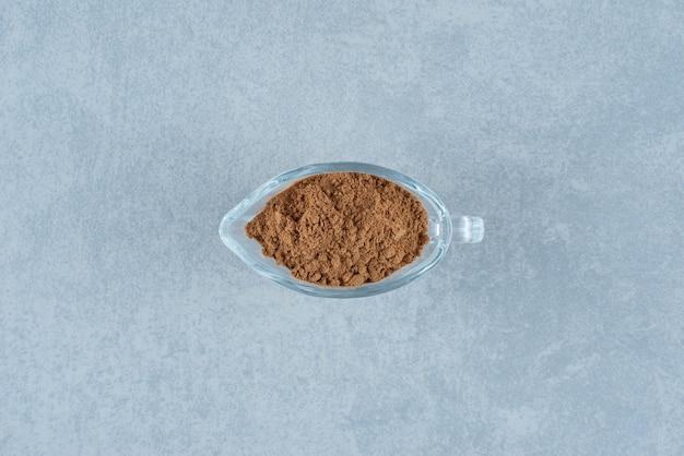 Poudre de cannelle mélangée dans une tasse en verre. photo de haute qualité