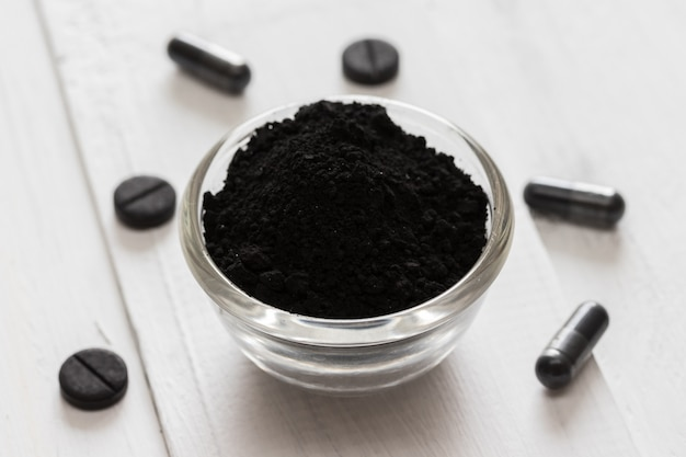 Poudre de charbon actif dans un bol en verre et des pilules sur un fond en bois blanc