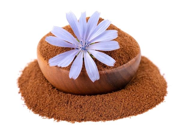 Poudre de chicorée et fleur dans un bol en bois isolé sur fond blanc cichorium intybus